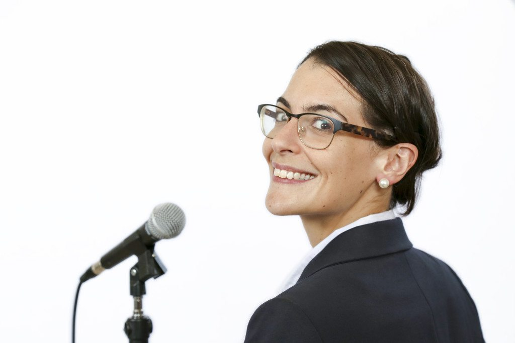 Sucssesful businesswomen keynote speaker in front of microphone before public speaking