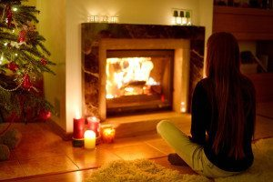 Young woman by a fireplace in a cozy dark living room on Christmas eve