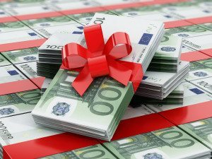 100 euro bills stack wrapped with red ribbon.