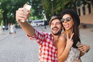 Beautiful hipster couple making selfie photo on a background of the city on summer day
